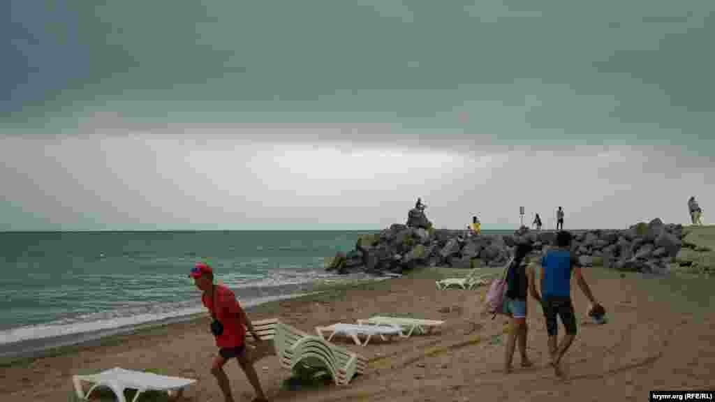 Работники пляжа убирают шезлонги перед дождем