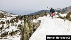 Скиор в ски обувки със ски, закачени на раницата, се качва към връх Бъндеришки чукар в Пирин