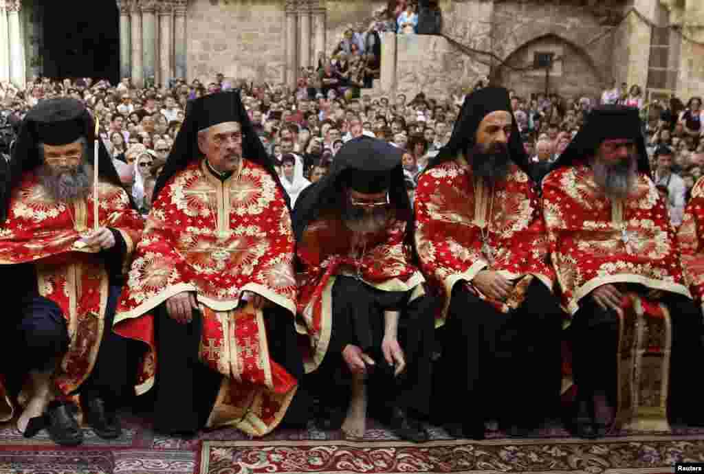 A Greek Orthodox priest puts his shoe back on during the washing of the feet ceremony outside the Church of the Holy Sepulchre in Jerusalem's Old City ahead of Orthodox Easter. (Reuters/Ammar Awad)