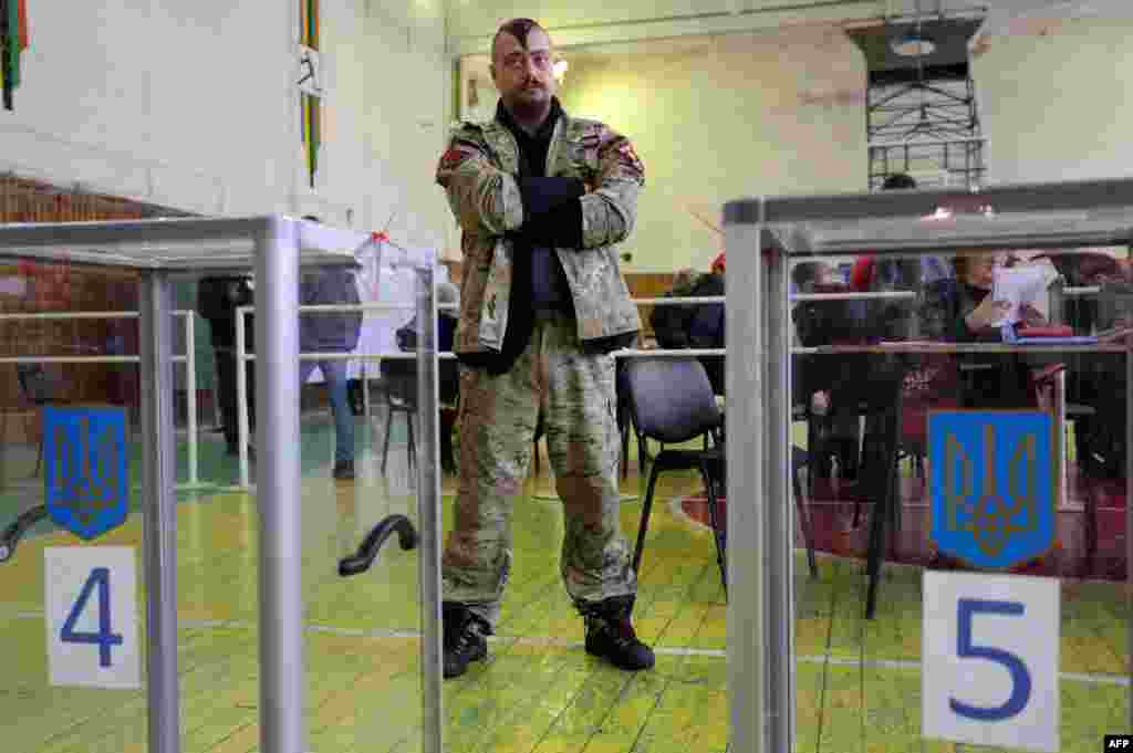An election observer of the far-right Ukrainian party Right Sector stands at a polling station in Mariupol, in the Donetsk region, during postponed local elections on November 29. (AFP/Aleksey Filippov)