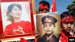 Aung San Suu Kyi-ni dəstəkləyənlər onun (arxada) və atası general Aung San-ın (öndə) plakatlarını tutublar