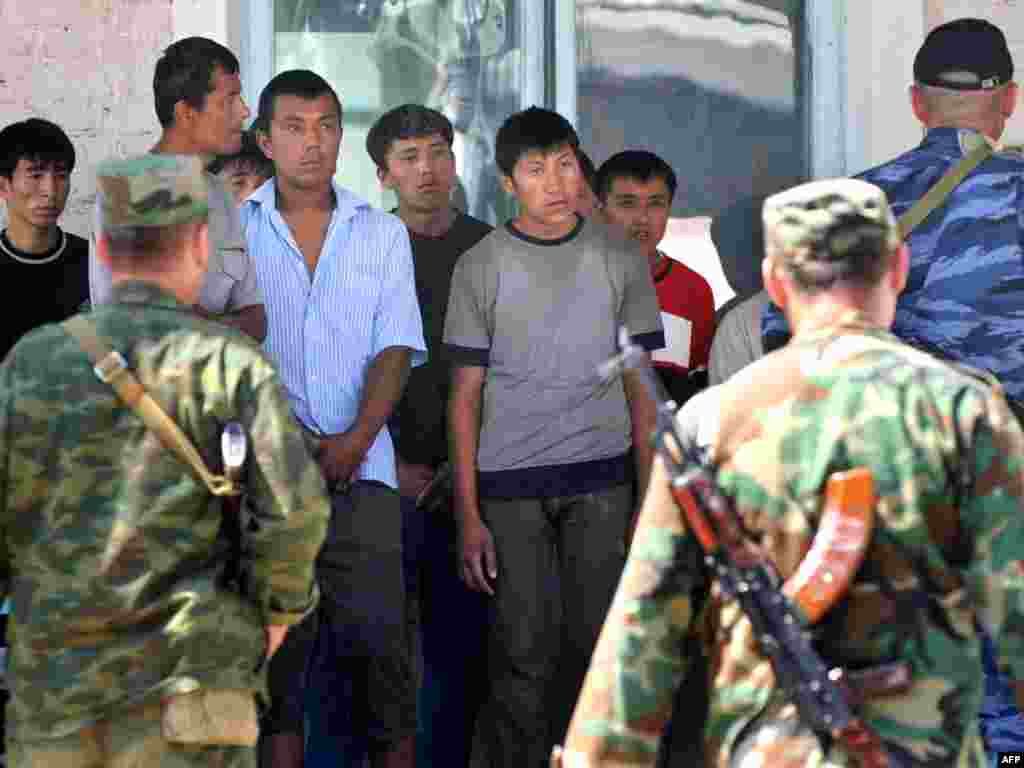 Security forces search detained ethnic Uzbeks after a military operation in the village of Nariman.