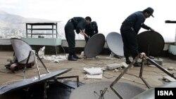 Иранские полицейские демонтируют спутниковые антенны, установленные на крыше здания.