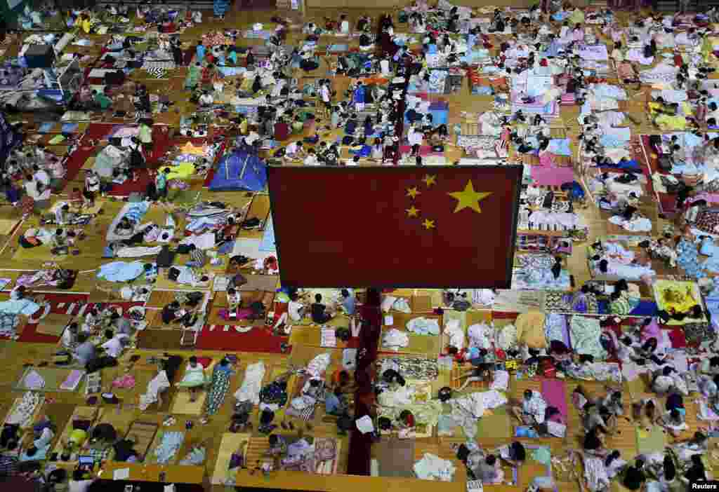 Students prepare to sleep on mats laid out on the floor under a Chinese national flag inside a gymnasium at the Huazhong Normal University in Wuhan, Hubei Province, China. More than 1,000 students slept inside the gymnasium to escape the hot weather in Wuhan, which reached 35 degrees Celsius on June 29. (Reuters/Stringer)