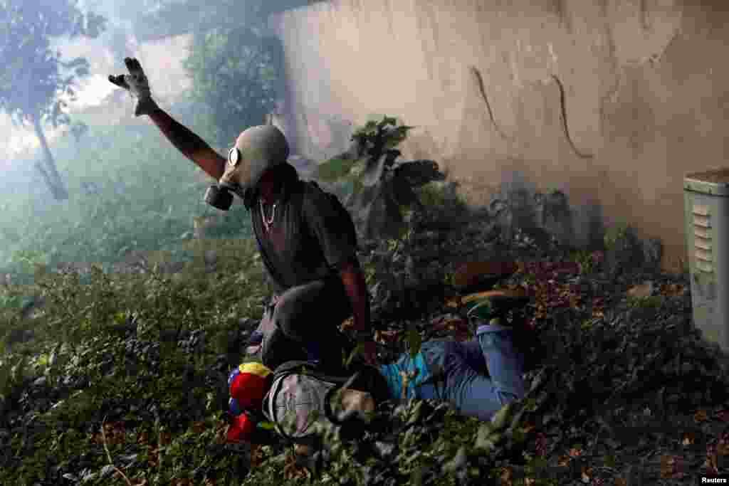 Паранены дэманстрант дапамагае іншым пратэстоўцам пасьля сутыкнення з паліцыяй падчас «Маці ўсіх маршаў» супраць прэзыдэнта Нікаласа Мадуры ў Каракасе 19 траўня.