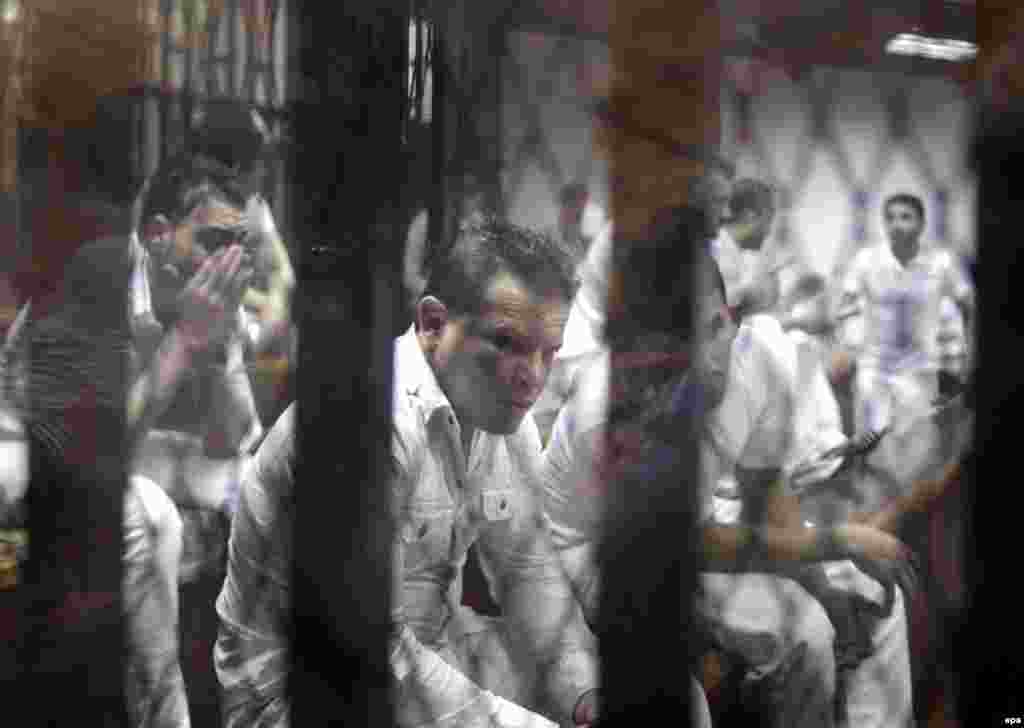 Defendants on trial for deaths in a riot following a football match in Port Said in February 2012 stand behind bars during their trial in Cairo. An Egyptian court on June 9 confirmed the death sentences of 11 men for their part in the country's worst-ever football-related violence. The February 2012 riots left 74 dead. (epa/Khaled Elfiqi)