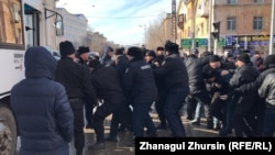 Полиция көшеден ұстаған адамдарды көлікке күштеп салып жатыр. Ақтөбе, 22 ақпан 2020 жыл.