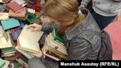 KitapFest-2015 шарасында кітап қарап отырған қыз. Алматы, 5 қыркүйек 2015 жыл.