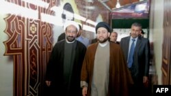 A picture taken in 2010 shows Lebanese Shiite cleric Muhammad Kawtharani (L), who has long spearheaded Hezbollah's Iraq policy, alongside Iraqi Shiite Muslim leader and head of Hikma party Ammar al-Hakim (C) during a visit to the gravesite of assassinated