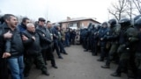 UKRAINE -- Demonstrators line up in front of Ukrainian law enforcement officers as they protest the arrival of a plane carrying evacuees from China's Hubei province hit by an outbreak of the novel coronavirus in the village of Novi Sanzhary in Poltava reg