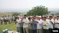 People pray during the burial of murdered human rights activist Natalya Estemirova at a cemetery in Koshkeldy, 70 kilometers east of Grozny, on July 17, 2009.