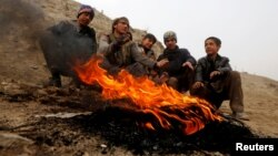 Afghan youth warm themselves by a fire during a cold day on the outskirts of Kabul last week.