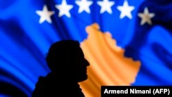 A man stands in front of a screen displaying the Kosovo flag in Pristina.