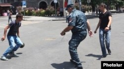 Armenia - A police officer plays football with protesters on Marshal Bagramian Avenue, Yerevan, 25June2015.