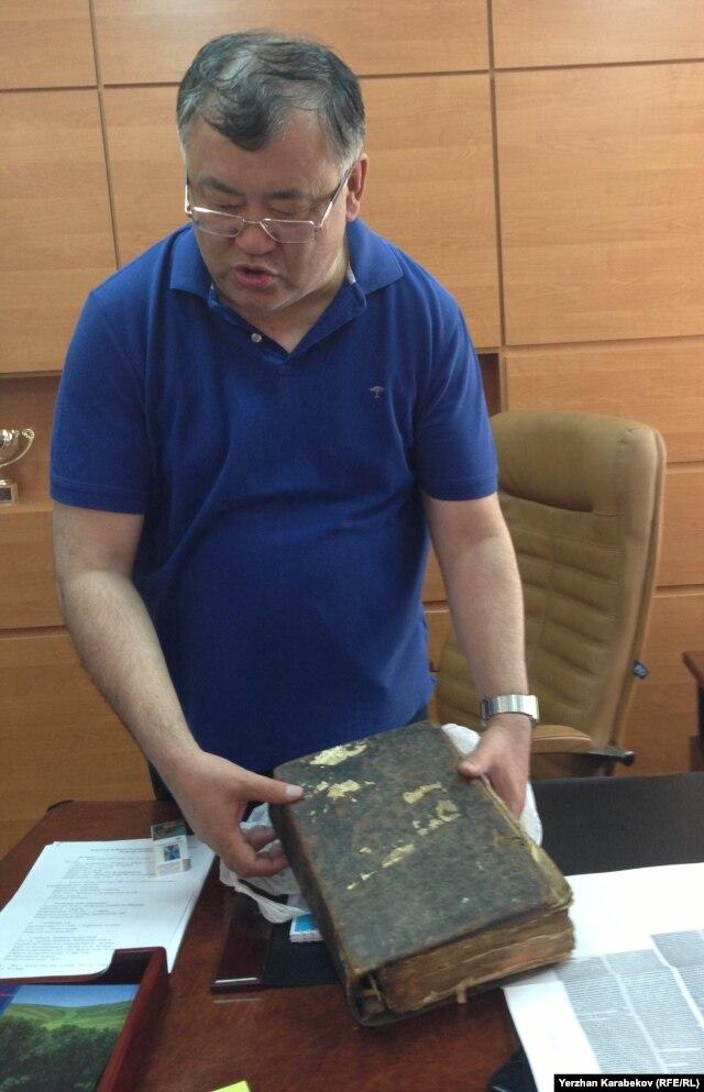 Руководитель научно-исследовательского проекта университета «Карлаг: память во имя будущего» профессор Нурлан Дулатбеков показывает Библию, которая хранилась у политзаключенной в Кенгирском лагере. Караганда, 7 июня 2015 года.