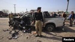 Polici pakistanez e shikon veturën e dëmtuar pas një sulmi në Peshavar