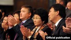 Then-parliament speaker Akmatbek Keldibekov (center left) stands next to former Kyrgyz President Roza Otunbaeva (center) at an early-October event.