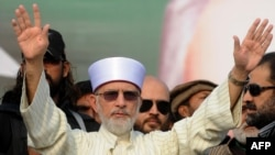 Muhammad Tahir-ul-Qadri waves to supporters on his arrival in Lahore on December 23.