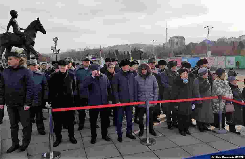 Чиновники во главе с акимом Алматы Бауржаном Байбеком (в центре) на церемонии возложения цветов к монументу Независимости. Алматы, 16 декабря 2018 года.