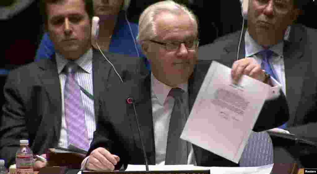 Vitaly Churkin, Russian ambassador to the UN, shows a letter to the UN Security Council on March 3 purportedly from ousted Ukrainian leader Viktor Yanukovych to Vladimir Putin asking the Russian leader for military intervention in Ukraine. (Reuters)