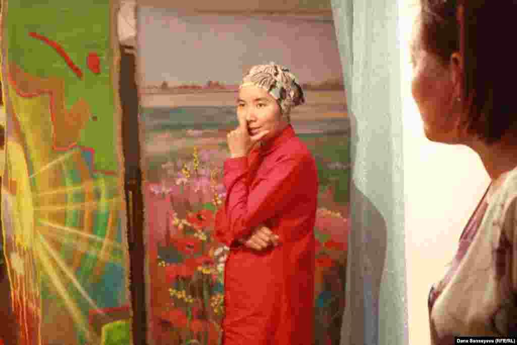 """Художник Гульмира Татимбаева на фоне своих картин отвечает на вопросы гостей """"квартирника""""."""