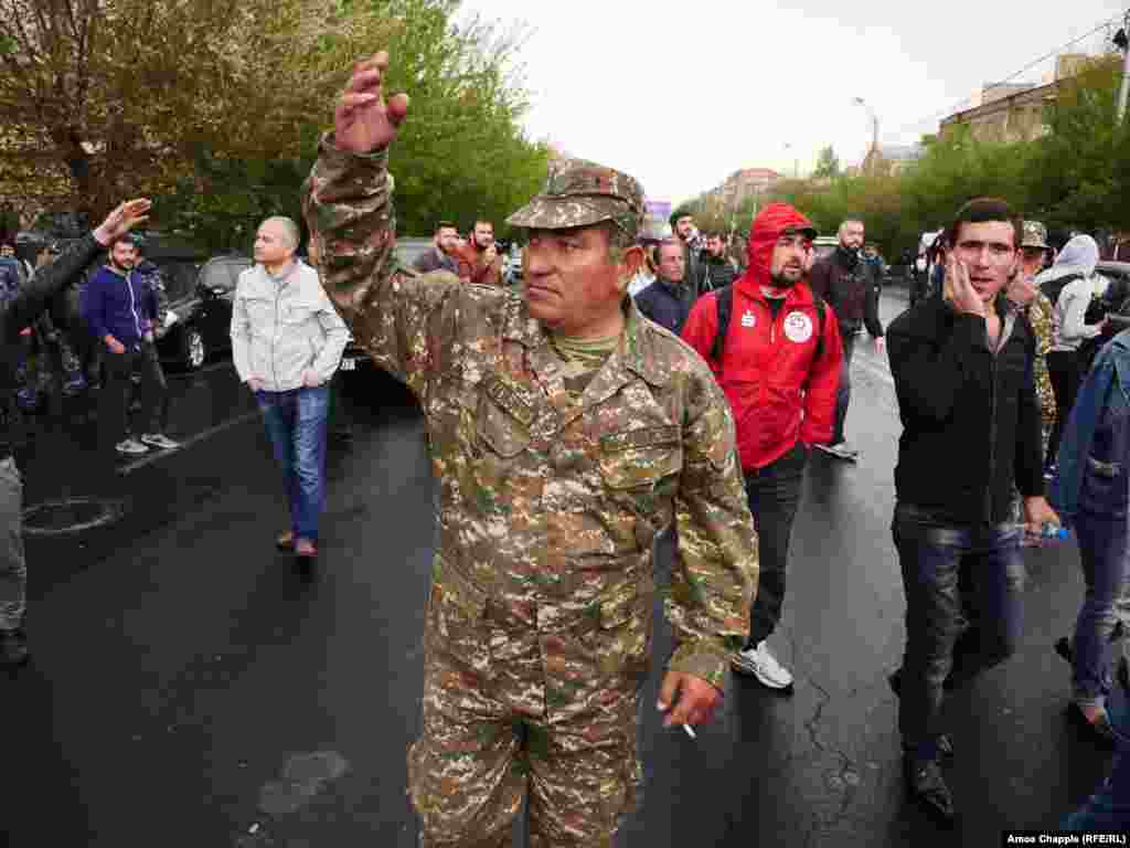 A man wearing an Armenian army uniform gestures at a line of police, encouraging them to join the protest.