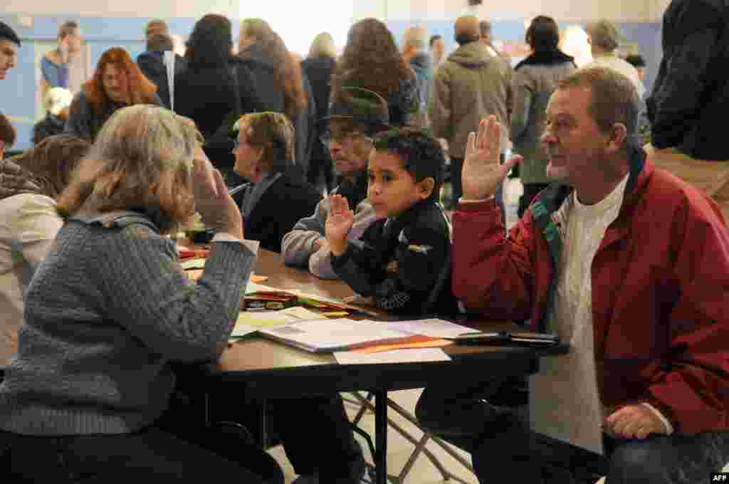 Tom Hoisington (right) raises his right hand after being registered to vote at the Bishop Leo O'Neil Youth Center in Manchester, New Hampshire. Hoisington's grandson, Tonykus Hebert, mimics his grandfather.