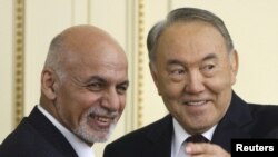 Kazakh President Nursultan Nazarbaev (R) and Afghan President Ashraf Ghani smile as they arrive for a news conference after their meeting at the Akorda presidential residence in Astana on November 20.