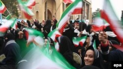 Iranian students wave national flags at the Behesht-e Zahra cemetery in Tehran on February 1.