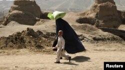 Афганская женщина идет с сыном. Кабул, 5 апреля 2012 года.