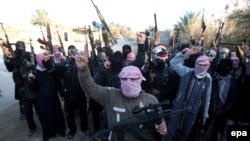 Masked Sunni gunmen shout slogans against the Iraqi Shi'a-led government during a protest in Fallujah on January 7.