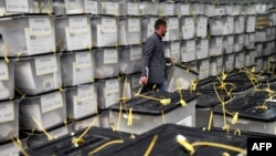 Kosovo -- An electoral official arranges ballot boxes at a counting center near Pristina, November 5, 2013