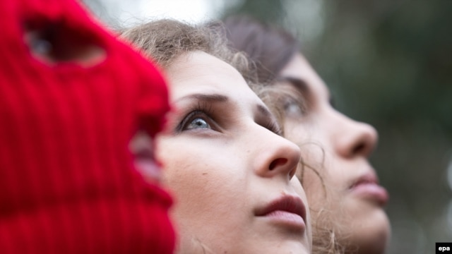 Nadezhda Tolokonnikova (right) and Maria Alyokhina (center), and a masked Pussy Riot activist are pictured during a news conference held outside a hotel in a park in Sochi on February 20.