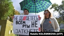 """A woman holds a placard reading, """"You can't shut up everyone!"""" as journalists and supporters take part in a protest against the """"foreign agent"""" law in central Moscow on September 4."""