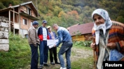 Bosnian Muslims speak with a census taker in the village Krusev Do, near Srebrenica on October 1