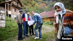Bosnian Muslims speak with a survey taker during Bosnia's first census in the village Krusev Do, near Srebrenica, in October 2013.