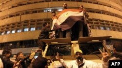 Egyptian demonstrators demanding the ouster of President Hosni Mubarak wave the national flag on top of an armored vehicle.