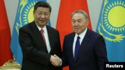 Kazakh President Nursultan Nazarbaev (right) and Chinese President Xi Jinping shake hands during a joint news conference following their meeting in Astana on June 8.