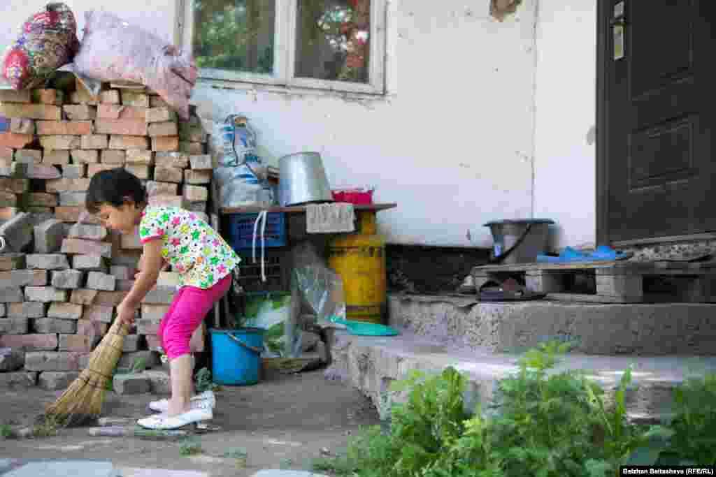 Пятилетняя Капиза пытается помогать матери, подметает во дворе.