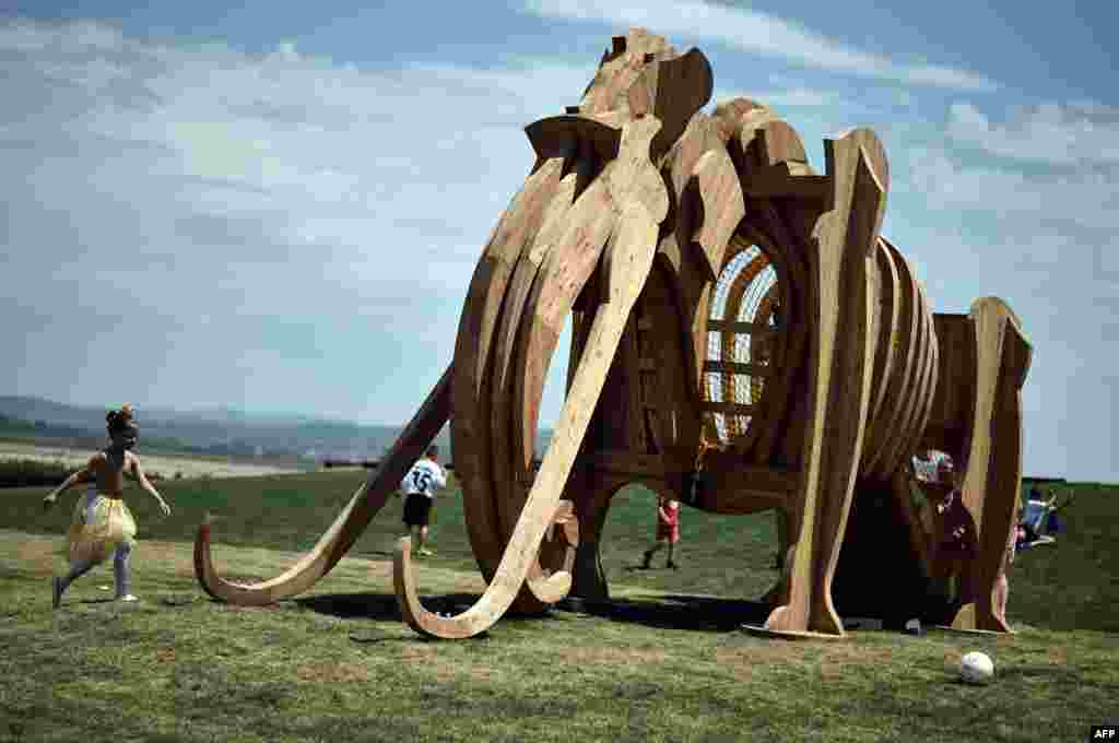Children run by a mammoth sculpture at the newly opened Mammoth Park near the town of Kostolac, some 100 kilometers south east of Belgrade, Serbia, on June 30. (AFP/Andrej Isakovic)