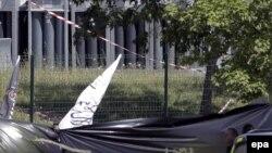 Паліцыянты нясуць сьцягі з надпісамі па-арабску на месцы здарэньня ў Францыі