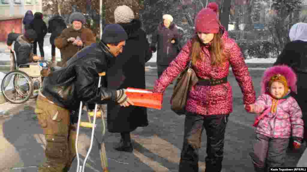 Рождество кезінде шіркеу алдында қайыр сұрап тұрған адам. Алматы, 7 қаңтар 2014 жыл.
