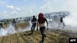 Полиция көзден жас ағызатын газ қолданған соң босқындар мен мигранттар қашып барады. Идомени, Грекия-Македония шекарасы, 10 сәуір 2016 жыл.