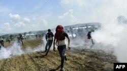 Слезоточивый газ в районе скопления мигрантов на участке границы Македонии и Греции. Идомени, 10 апреля 2016 года.