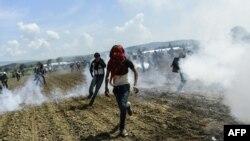 Мігранти утікають від розпиленого поліцією Македонії сльозогінного газу на кордоні, 10 квітня 2016 року