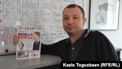 Аян Шарипбаев держит в руке первый номер журнала ADAM, главным редактором которого он является. Алматы, 13 марта 2015 года.