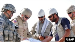 "U.S. and Afghan engineers review blueprints for a construction project in Farah Province. U.S. Undersecretary of Defense Michele Flournoy recently said that that U.S. ""troops can do astonishing things with even minimal resources, but they can't do magic."""
