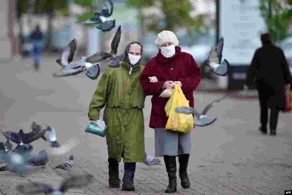 Two elderly women wearing face masks walk down a street in the town of Vitebsk, Belarus. (AFP/Sergei Gapon)