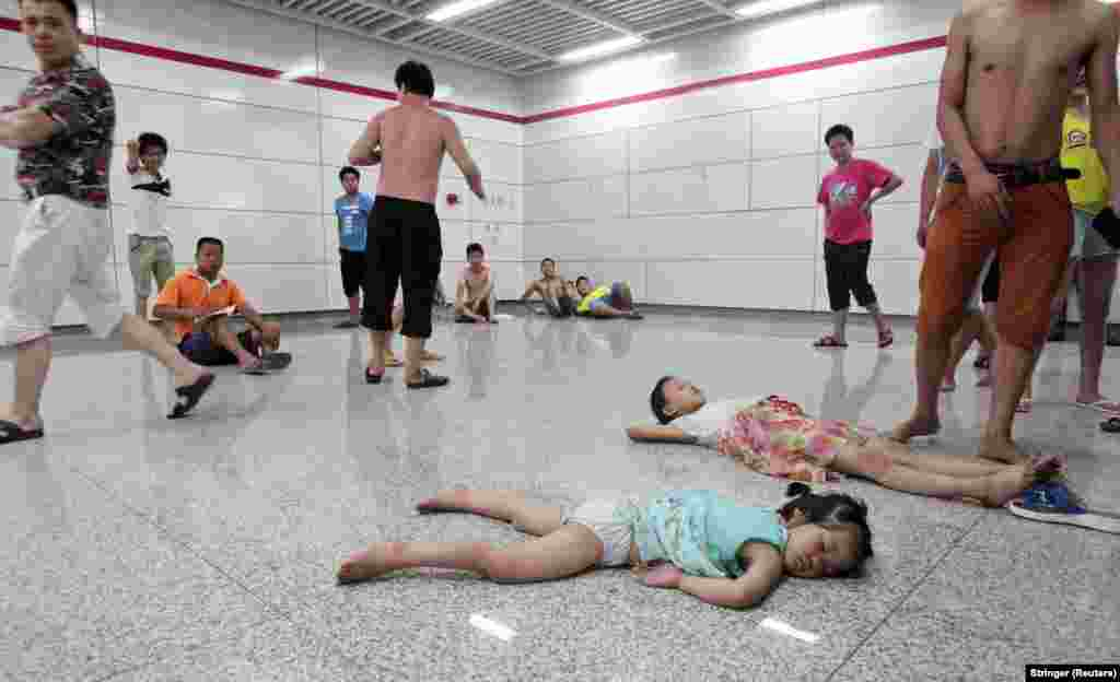 Children sleep on the floor of the Qiaosi subway station in Hangzhou in China's Zhejiang Province on July 26. Hundreds of people sought relief from the heat outside as temperatures in the city reached a high of 40 degrees Celsius and many homes were without power.