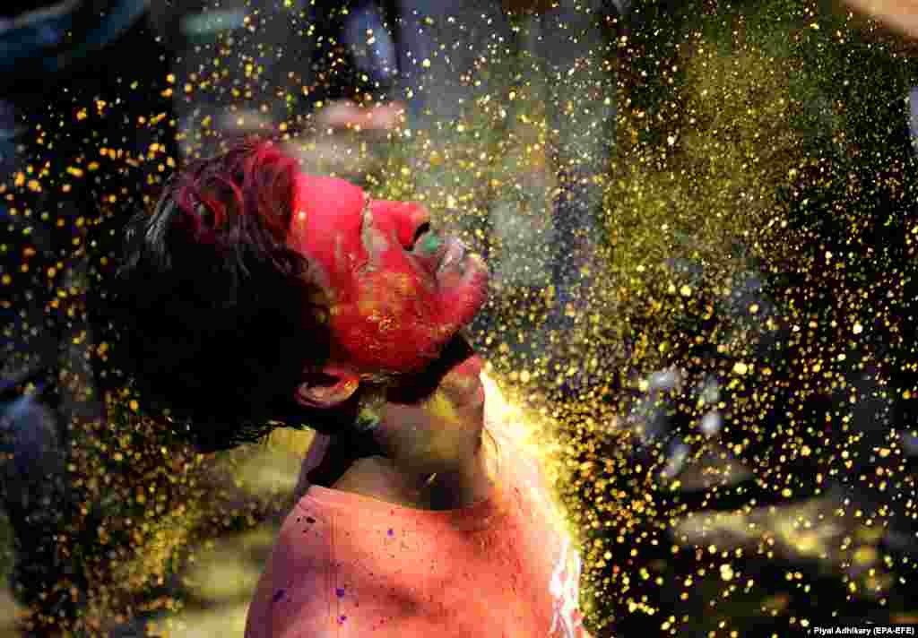 Locals apply colored powder on each other during Holi festival celebrations in Kolkata, India. (epa-EFE/Piyal Adhikary)